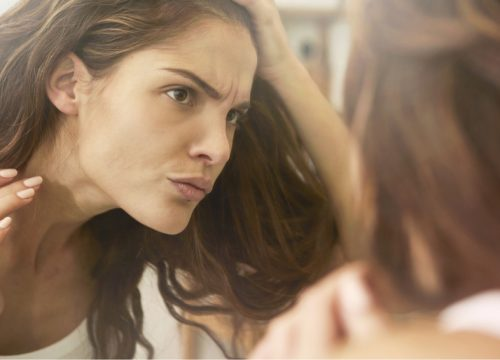 Woman looking at her wrinkles in the mirror